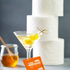 Quarantini in a glass with toilet paper and vitamin c.