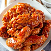 Sticky Chicken Tenders on a white plate.