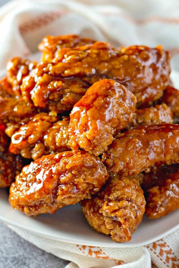 Sweet and spicy sticky chicken tenders on a plate.