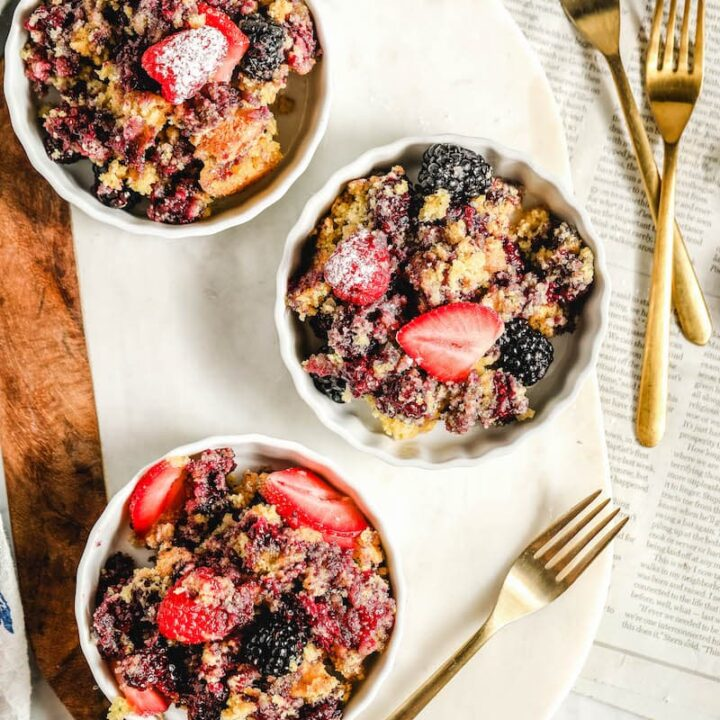 Blackberry cobbler served in 3 dishes and topped with sliced strawberries.