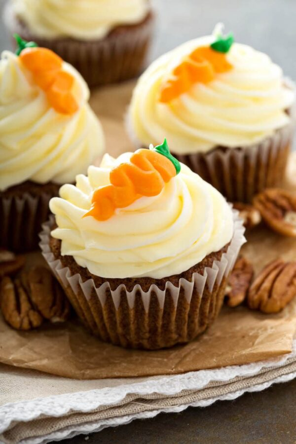 Three carrot cake cupcakes with a carrot on top.