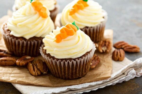 Carrot Cake Cupcakes with pecans and carrots on top.