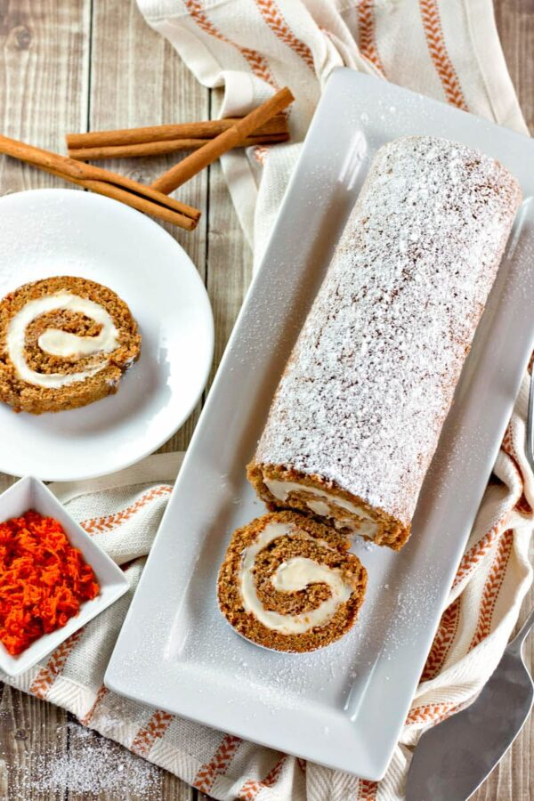 A sliced carrot cake roll with one slice on a plate.