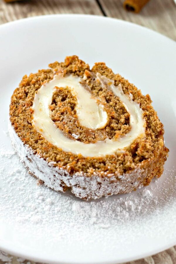 A slice of carrot cake roll dusted with powdered sugar.