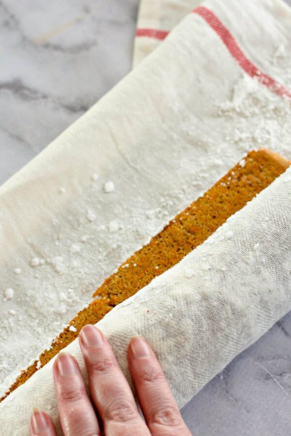 A warm carrot cake being rolled to cool.