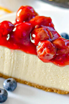 Up close image of a slice of cheesecake with cherries.
