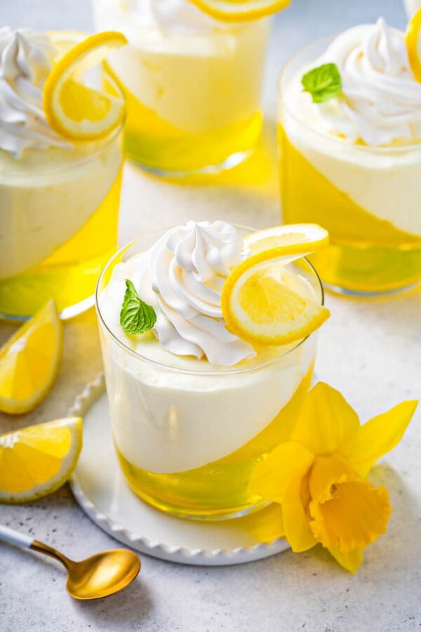 Lemon Mousse Jello Cups on plates with spoons.