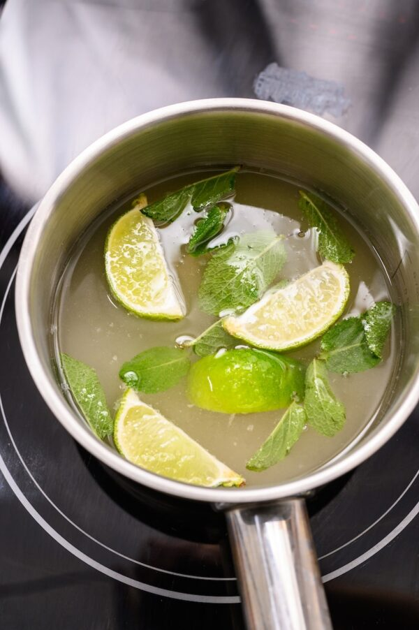 Mojito simple syrup with limes and mint floating in a pot.