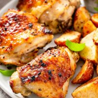 Perfectly baked chicken on a white plate with roasted potatoes.