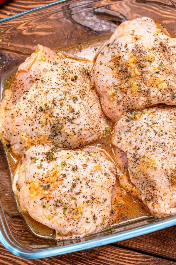 Raw bone-in skin on chicken breasts, seasoned and ready to be baked.
