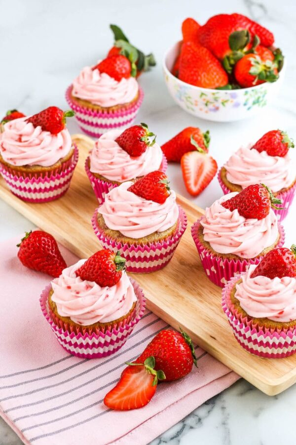 Strawberry cupcakes photographed from above with strawberries scattered about.