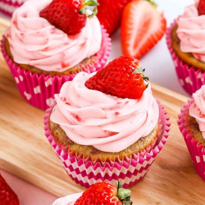 Close up image of 3 perfectly frosted strawberry cupcakes.