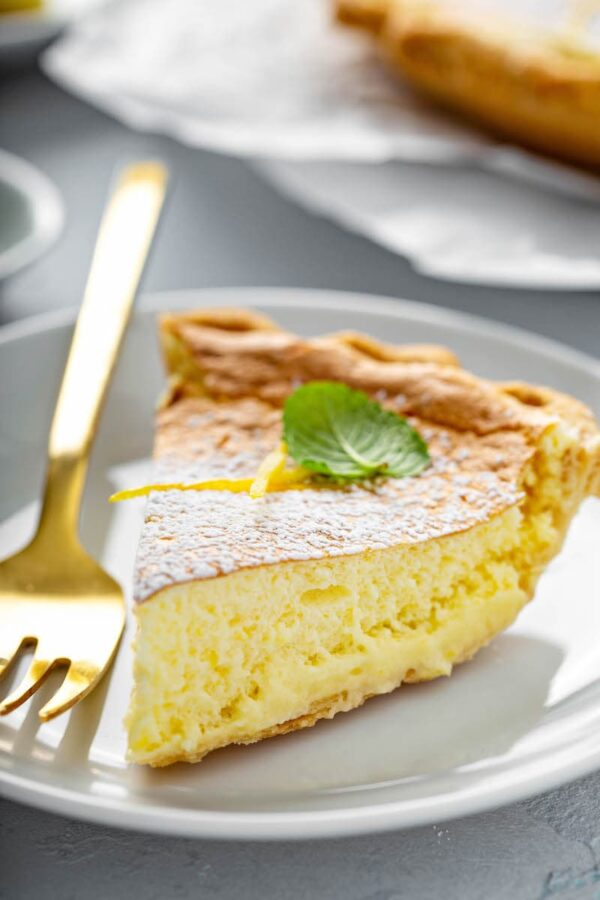 Slice of lemon pie on a white plate with a fork.