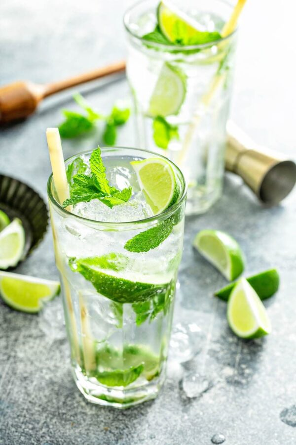 Two glass of mojitos with limes and mint scattered around the table.