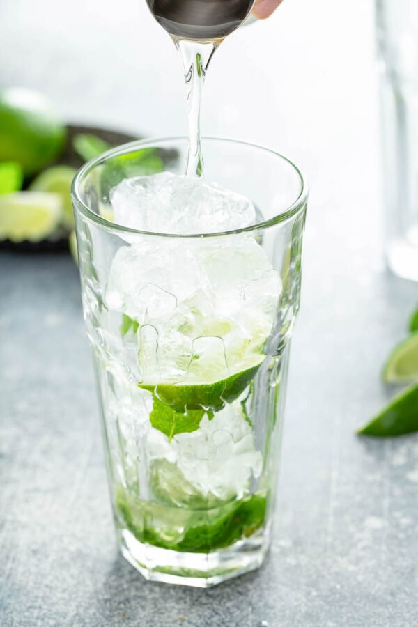 Simple syrup being poured into a glass with ice and lime wedges inside.