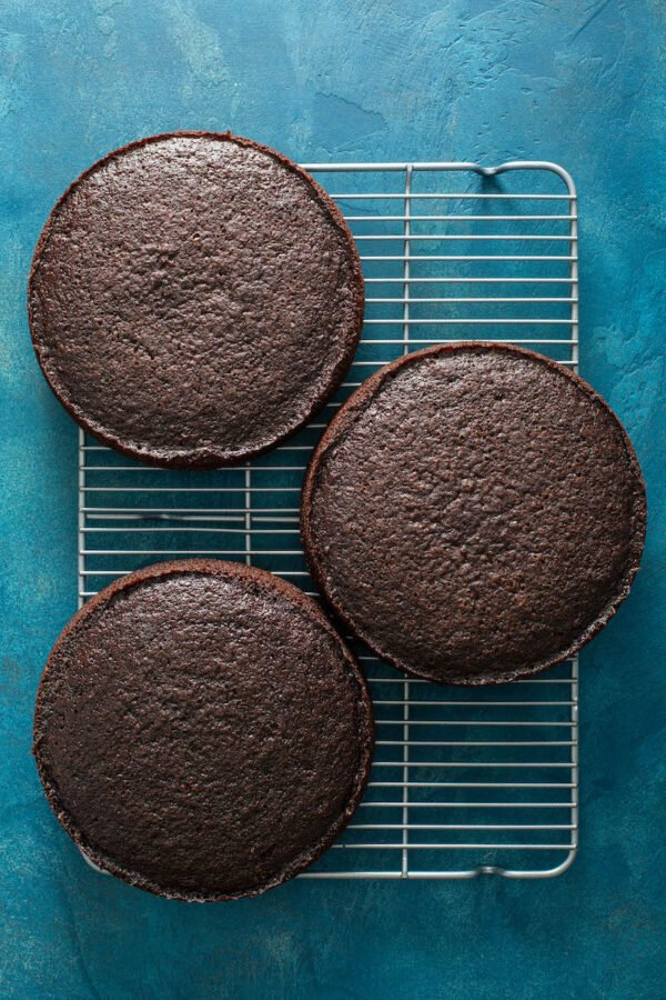 Three cooked layers of chocolate cake cooling on a bakers rack.