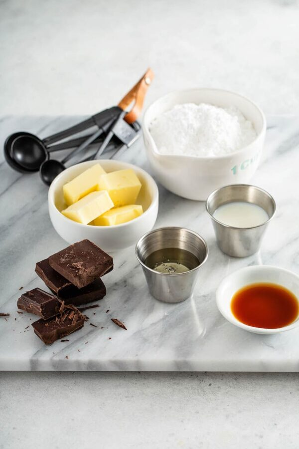 Ingredients in bowls for chocolate sauce on a marble countertop.