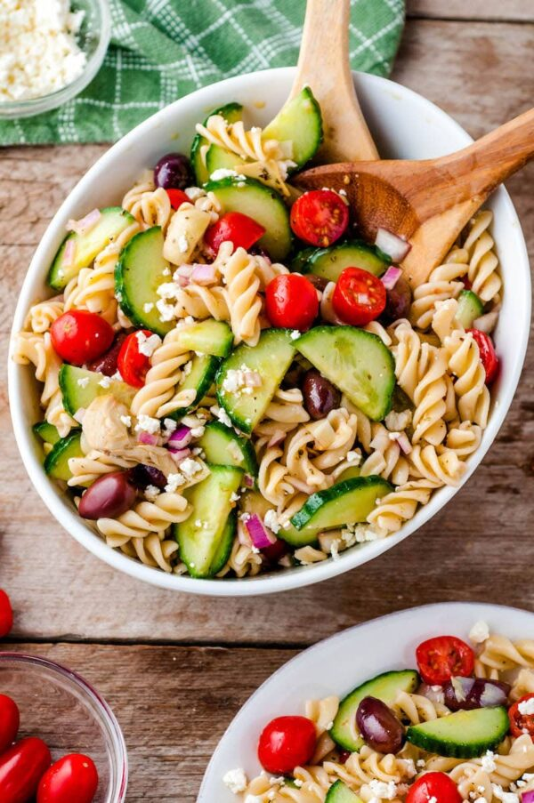 A bowl of Greek pasta salad with a spoon ready to serve.