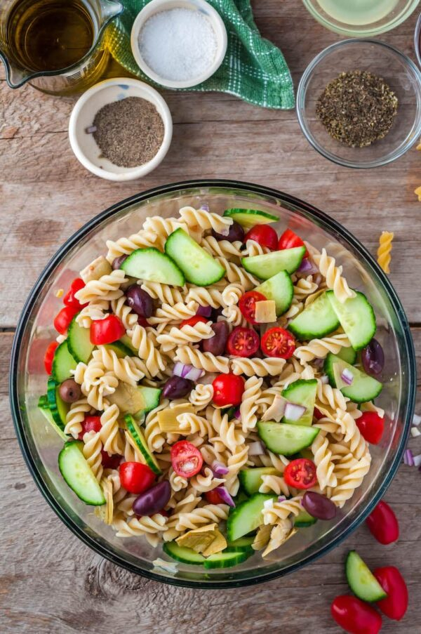 Greek pasta salad mixed together in a glass serving bowl.