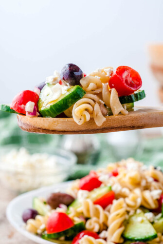 Greek pasta salad being served on a wooden spoon.