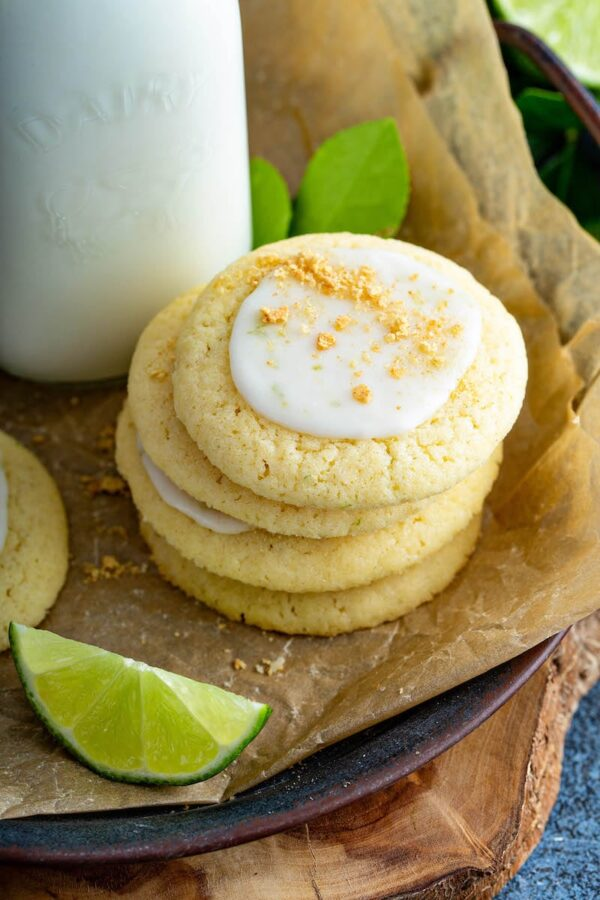 Stack of key lime cookies on parchment paper with milk and slices of limes.