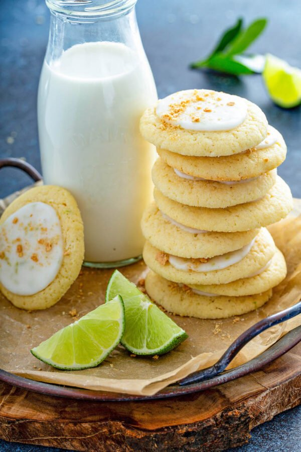 Key lime cookies stacked on top of each other with milk and limes on a plate with parchment paper.