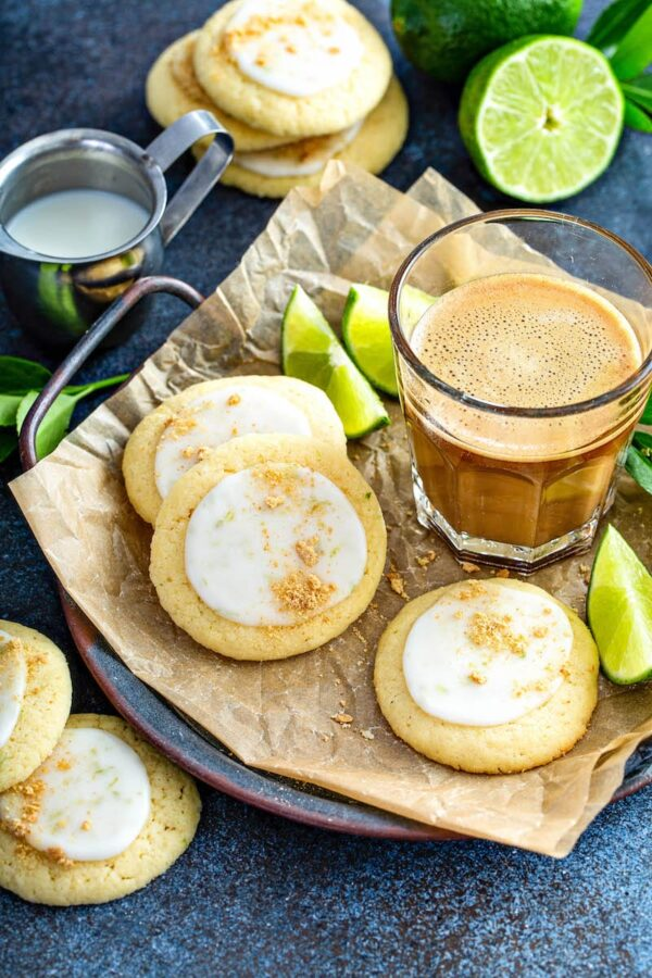 Key lime cookies on a plate with fresh limes and a cup of coffee.