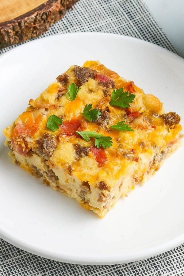 A slice of overnight breakfast casserole with sausage on a white plate.
