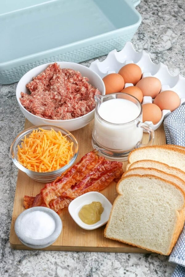 A wood cutting board with bread, bacon, sausage, eggs and cheese on top.
