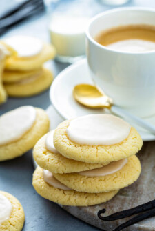 Vanilla meltaway cookies stacked on a plate with a cup of coffee and a gold spoon.