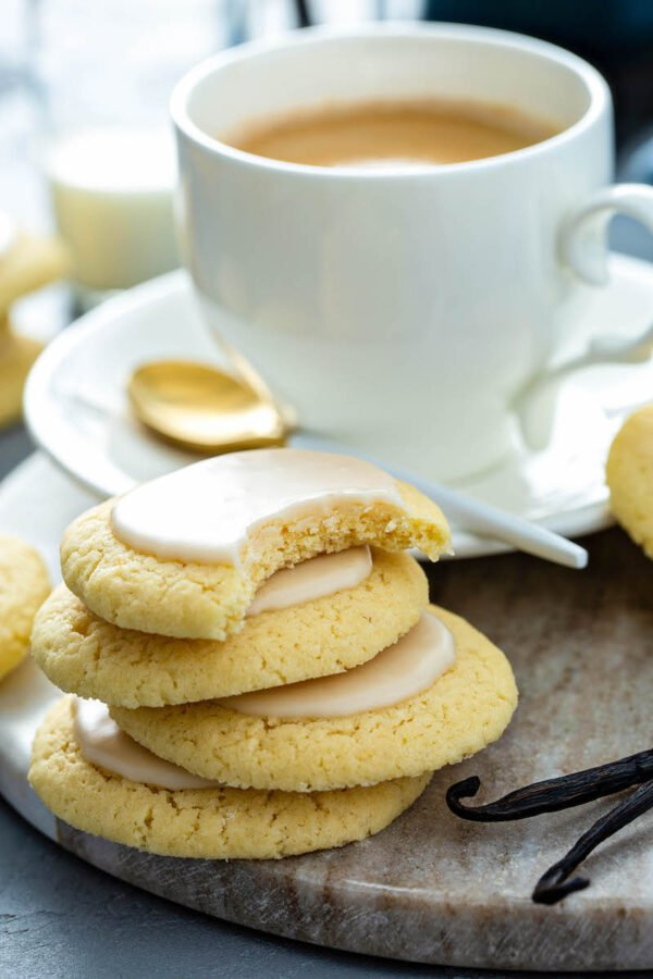 Vanilla meltaway cookies stacked on top of each other with a bite taken out of the top one and a cup of coffee in the background.