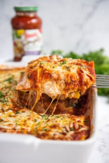 Ravioli Lasagna in a casserole dish sliced and being pulled out with a spatula.