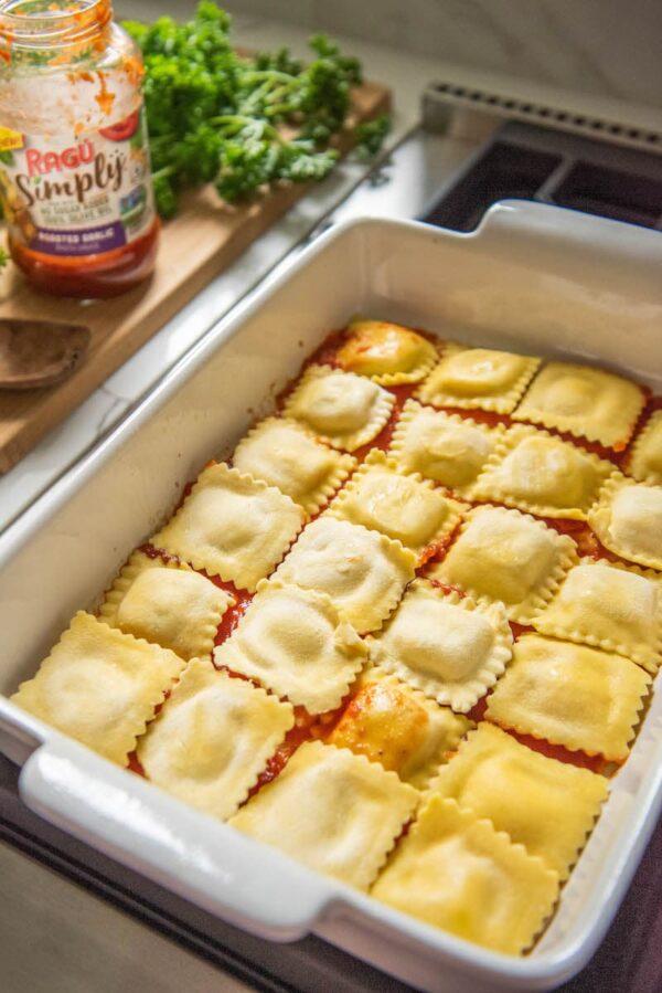 Ravioli lined in a 9x13 white casserole dish.