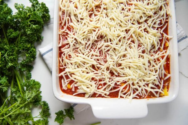 Ravioli lasagna in casserole dish topped with shredded mozzarella before baking.