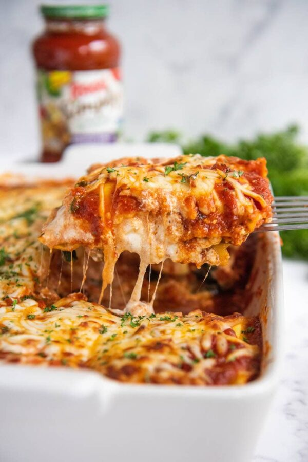 Ravioli Lasagna in a casserole dish sliced and being pulled out with a metal spatula.