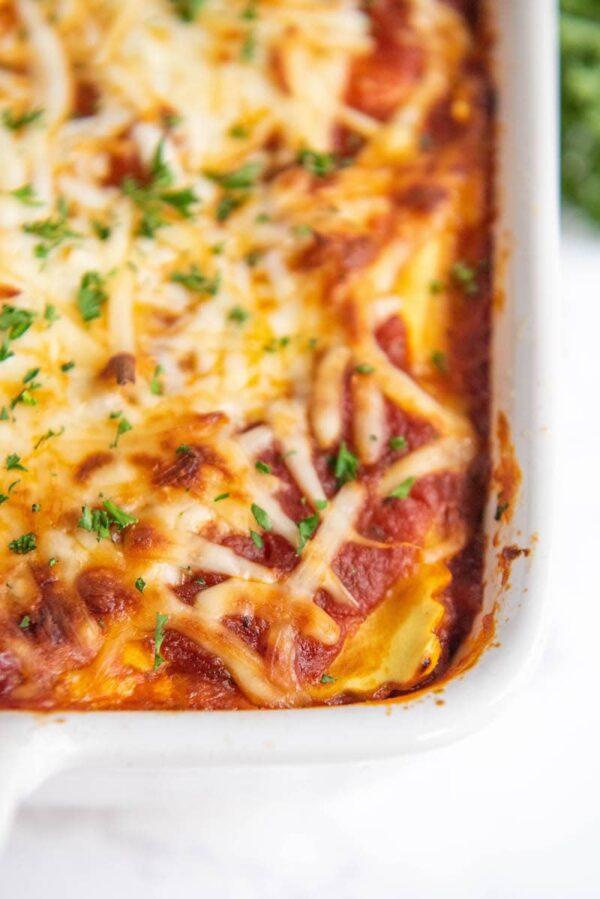 Up close image of ravioli lasagna in a white casserole dish.