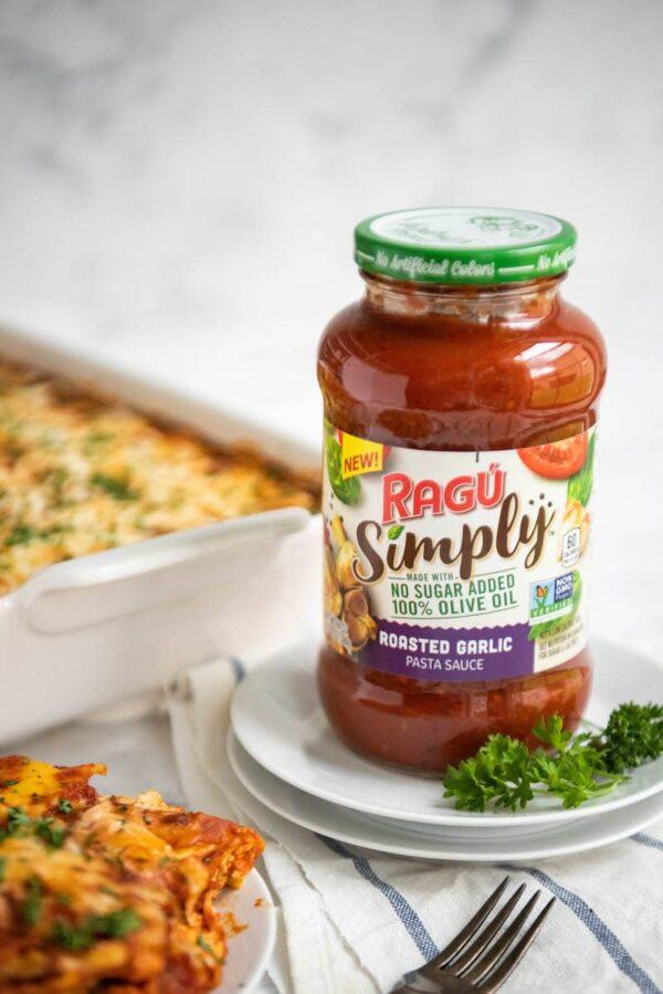 jarred marinara sauce on a stack of white plates with ravioli lasagna behind it