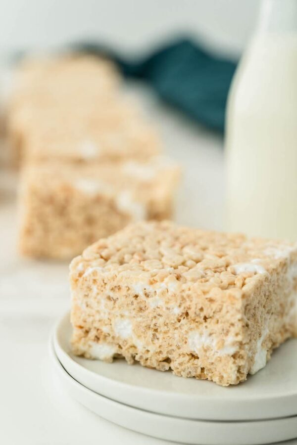 Rice krispie bar on a white plate with a cup of milk behind it.