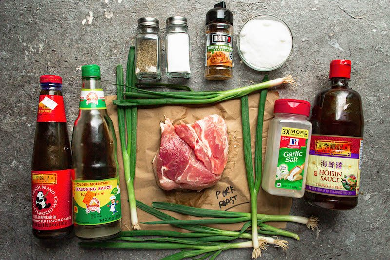 Ingredients arranged on a tabletop in bottles and pork on parchment paper.