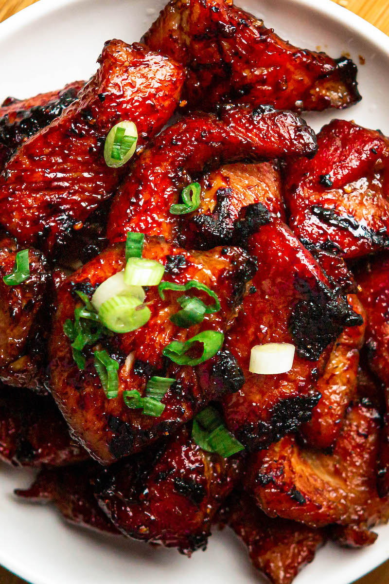 Char Siu on a plate with green onions on top.