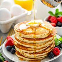 Stack of fluffy pancakes on a white plate with fresh fruit and syrup being poured on top of them.