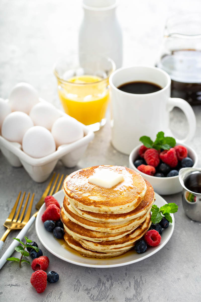 Favorite pancake recipe stacked on a plate with butter and syrup on top with coffee and orange juice in background.