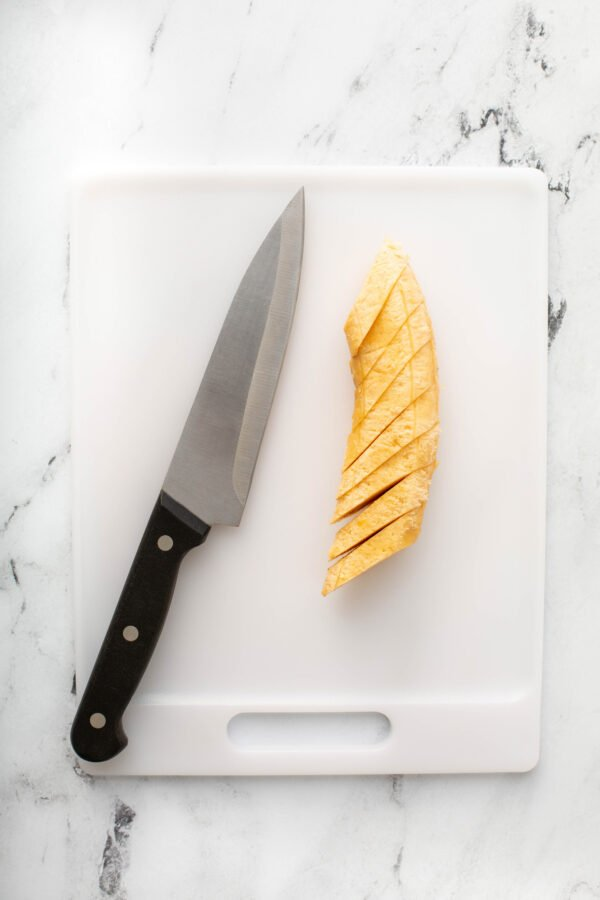 A Sliced Plantain with a Knife on a Cutting Board