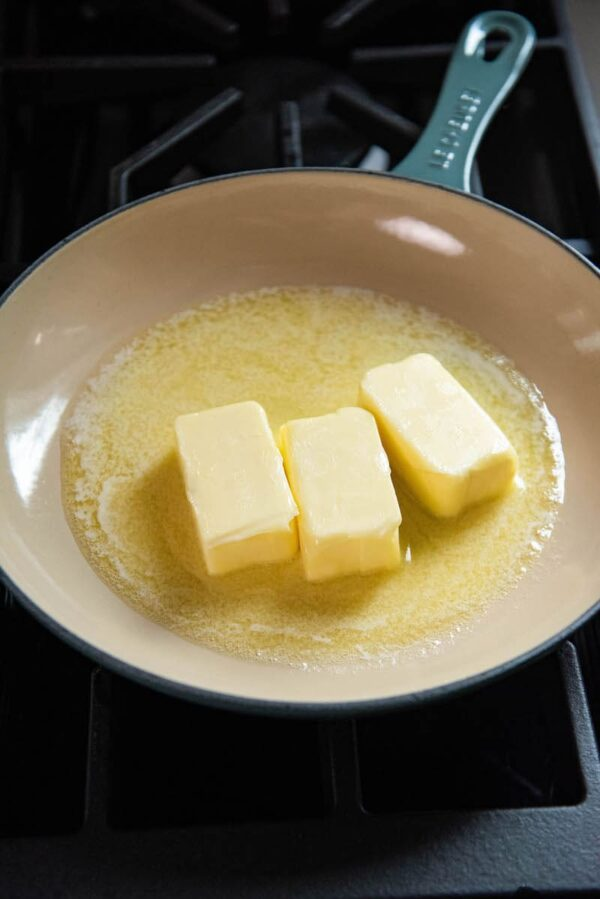 Three sticks of butter in a skillet,
