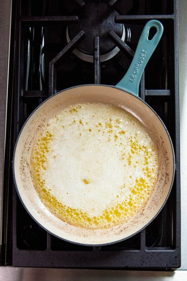 Melted butter in a skillet on a stove top.