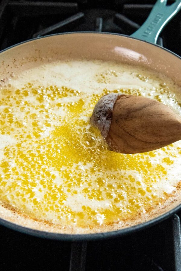 Bubbling butter in a skillet on a stove with a wooden spoon.