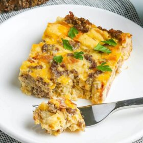 Up close image of overnight breakfast casserole on plate with a fork taking a bite of it.