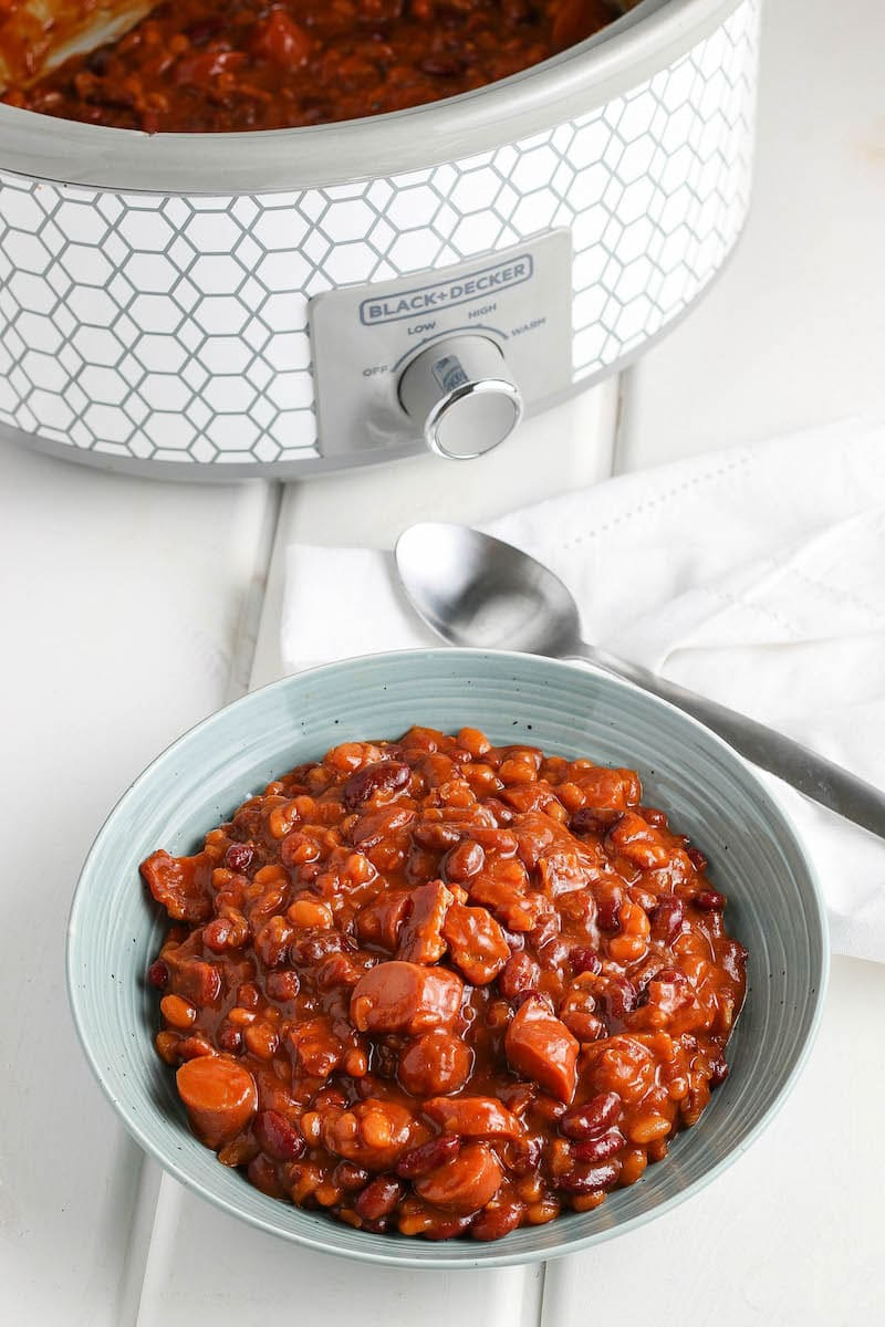 Franks and beans in a blue bowl with a crockpot and spoon in the background.