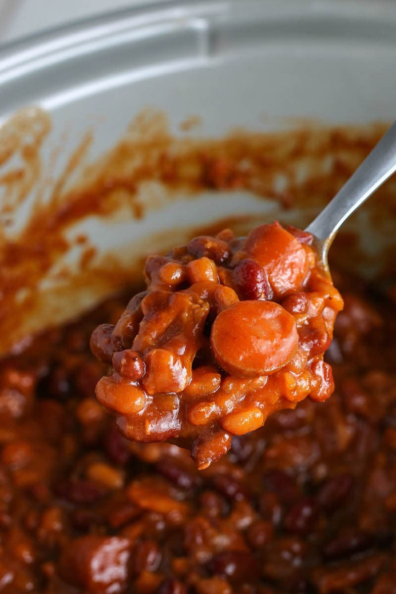 Pork and beans in a crockpot with a spoon.