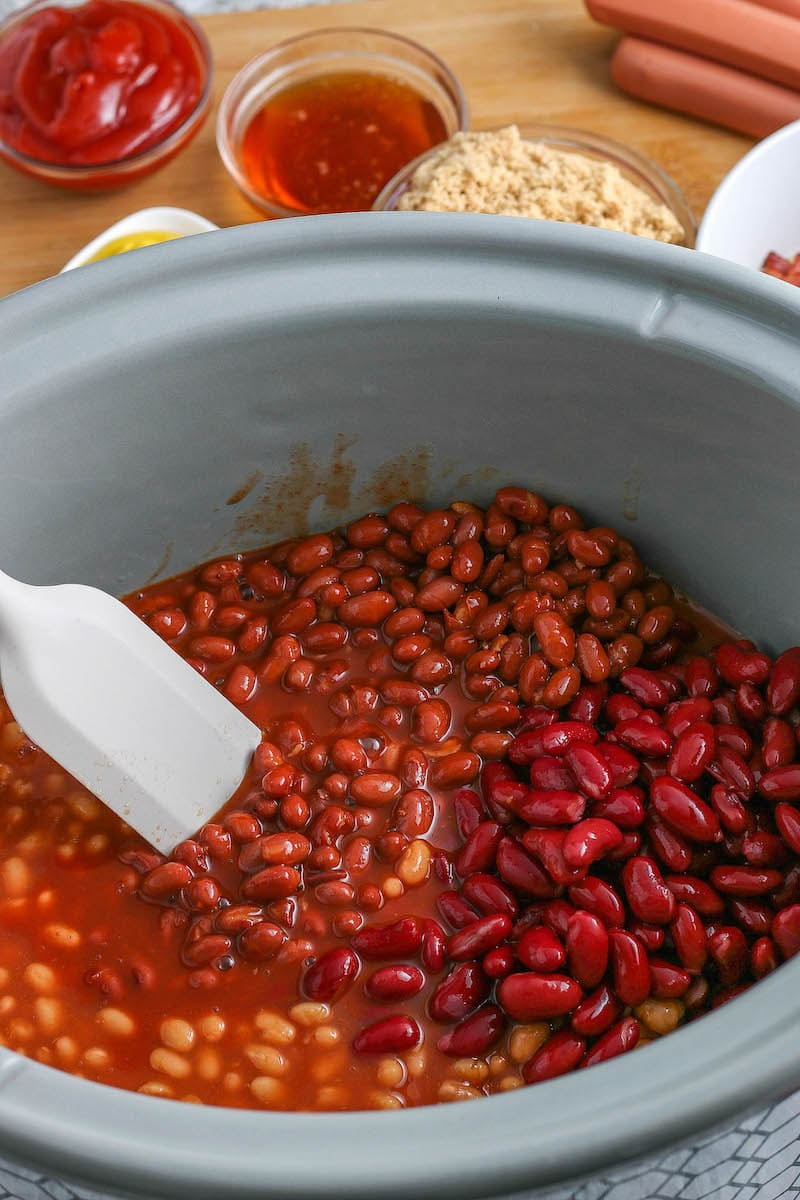 Different kinds of beans in a crockpot being stirred together.